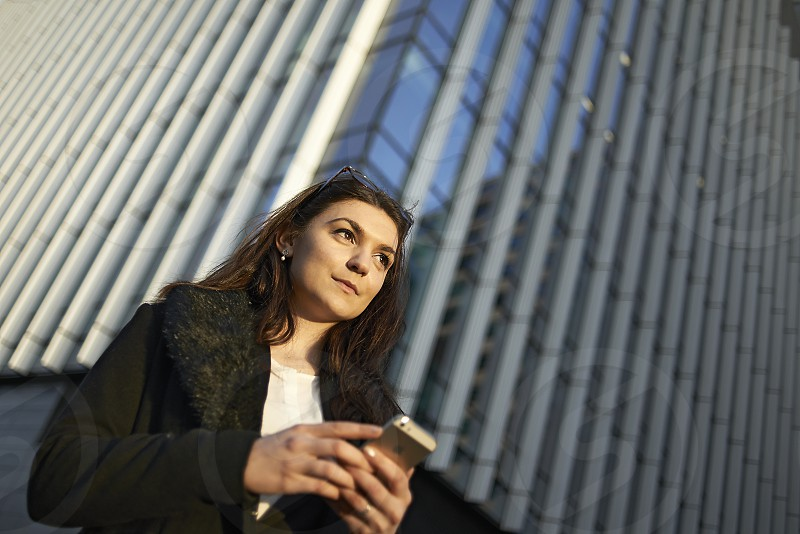 Young business woman in early morning sunlight using her mobile phone photo