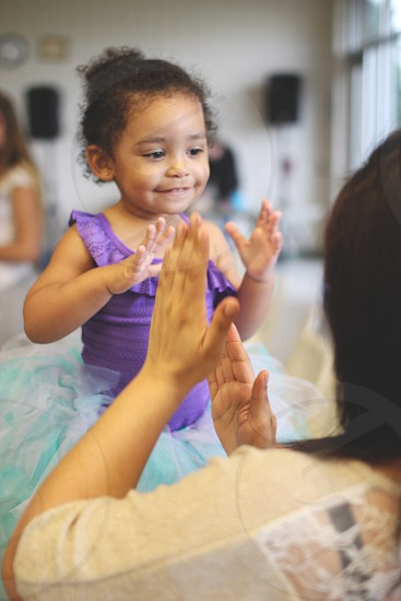 girl in purple tutu playing patty cake with woman photo