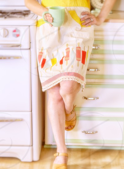 Unidentifiable  woman relaxing in retro kitchen holding coffee cup.  Bright springtime colors. photo