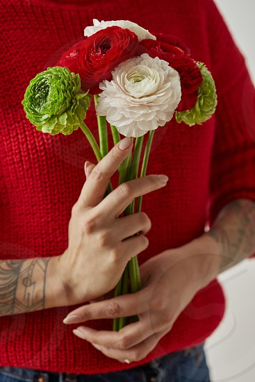 a bouquet of different flowers in the hands of a girl in a red knitted sweater and with a tattoo on her hands. Valentine's Day. Mother's Day. photo