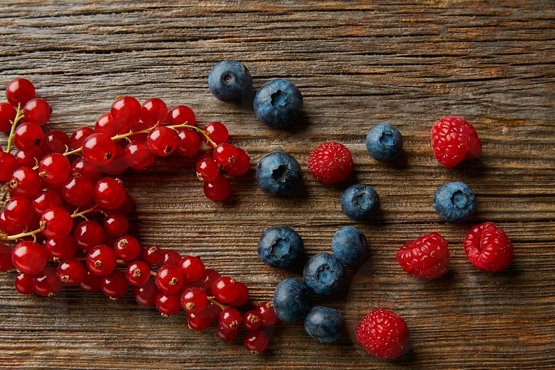 Berries mix on wooden board blueberries red currants and raspberries photo