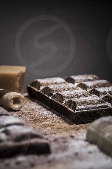 chocolate;bars; chocolates; white; dark; shiny; sparkly; decorated; dark background; wood; wooden; cinnamon; sticks; sugar; powder; sweet; food;  photo