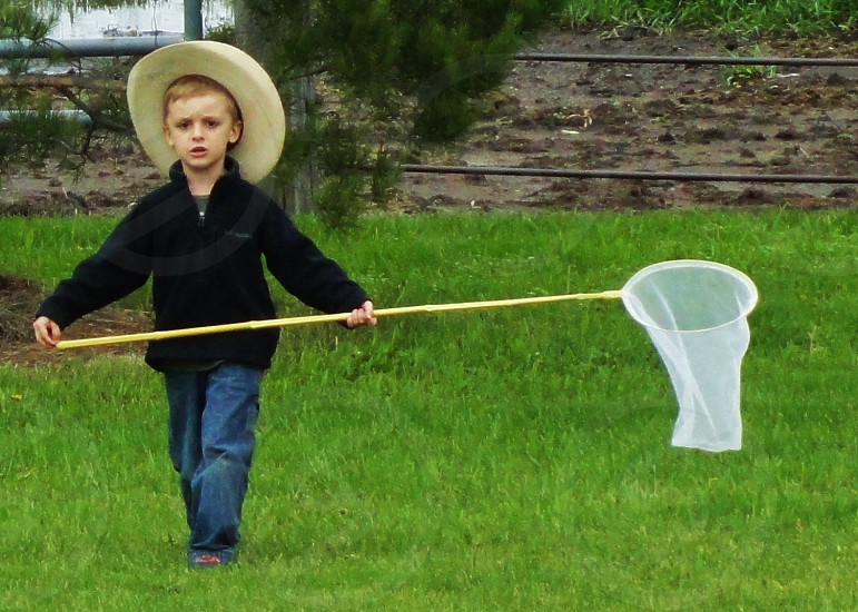 boy in black jacket walking and carrying insect net photo