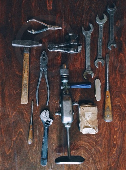 wrenches pliers hammer screwdrivers and hand drill on table photo
