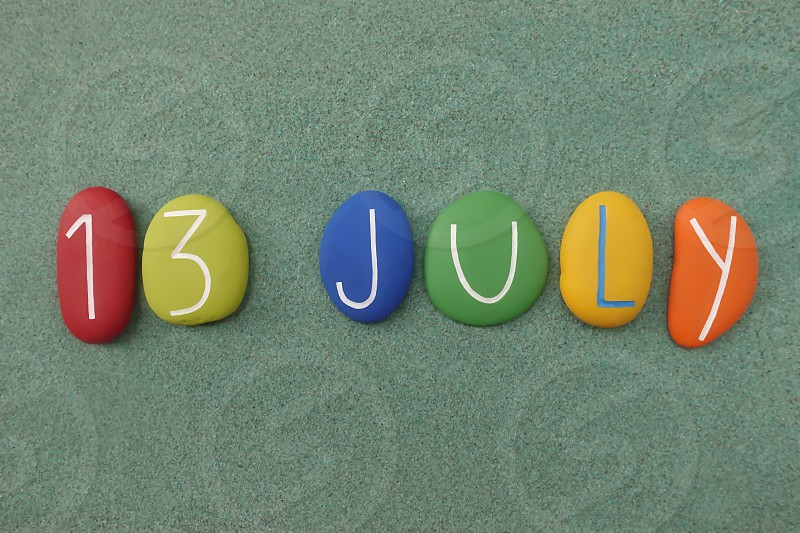 13 July calendar date composed with multi colored stones over green sand                        photo