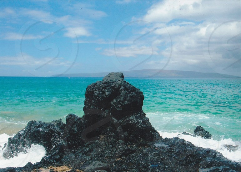 Large lava rock with beautiful ocean water in the background  photo