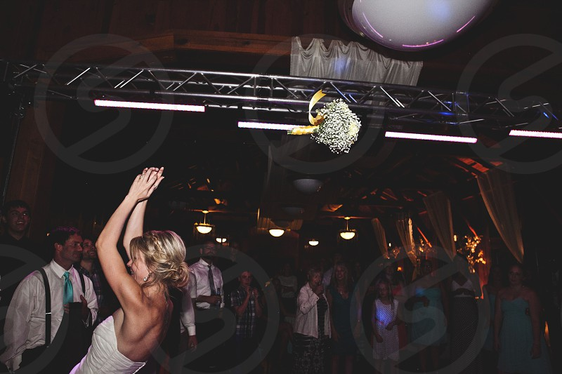 bride wedding reception bouquet toss flowers celebration tradition party throwing photo
