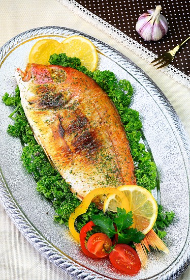 Cooked Whole white fish-off white table cloth background photo