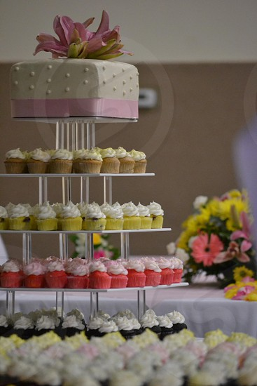 white fondant cake and cupcakes on 5 tier tray photo