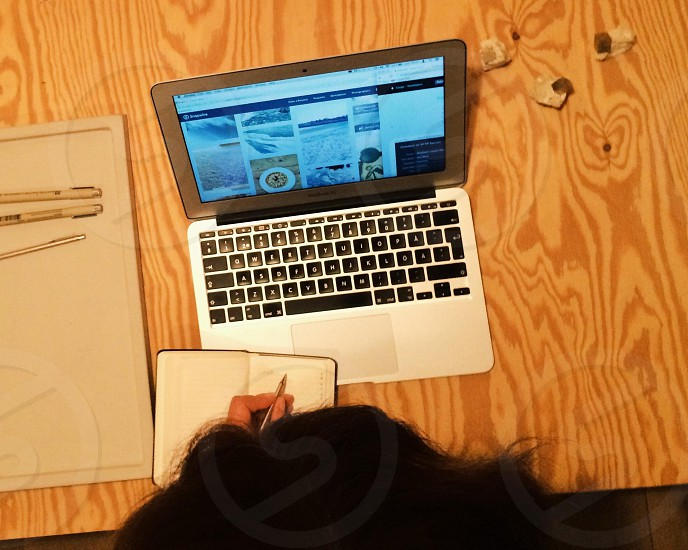 female at the desk in front of her lap top writing in a calendar shoot from above photo