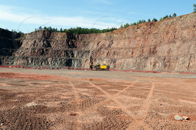 Driller in an open pit mine. porphyry rock material. photo