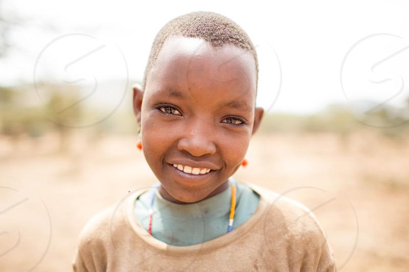 girl in brown shirt smiling during daytime photo