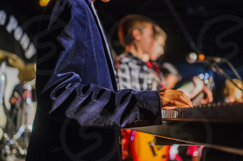 man in blue blazer playing piano photo