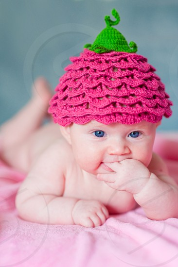 baby wearing pink and green knit cap lying on pink textile photo