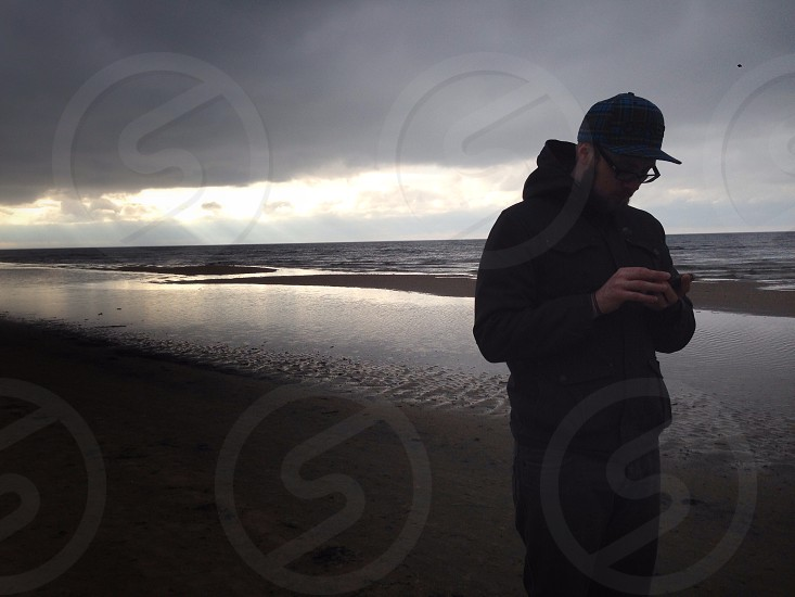 man wearing black pullover hoodie with black fitted cap using smartphone on seashore photo
