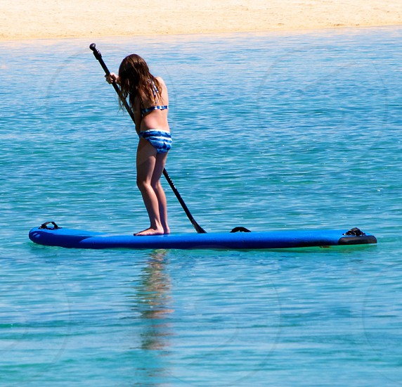 Young lady paddle boarding on the island of Oahu. Clear blue water.  photo