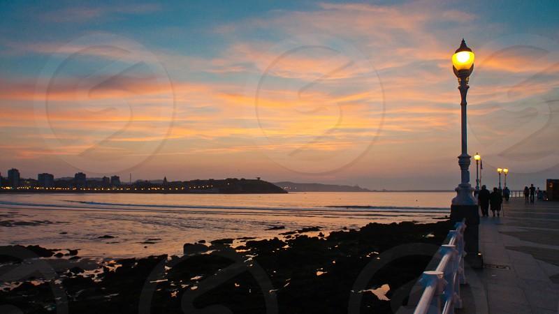 Boardwalk lights on at sunset photo