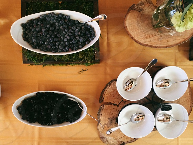 blueberries in bowl beside white ceramic bowls with spoons photo