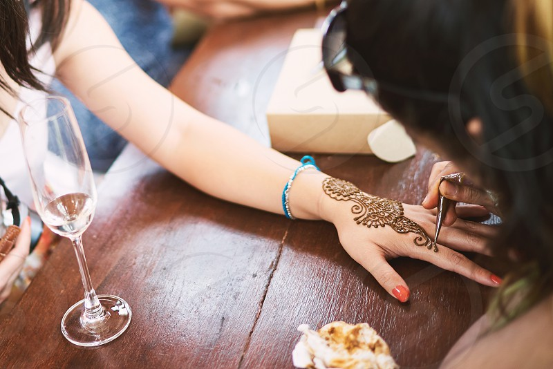 Indian henna tattoo artist painting the artwork on women foot on the indian wedding day photo