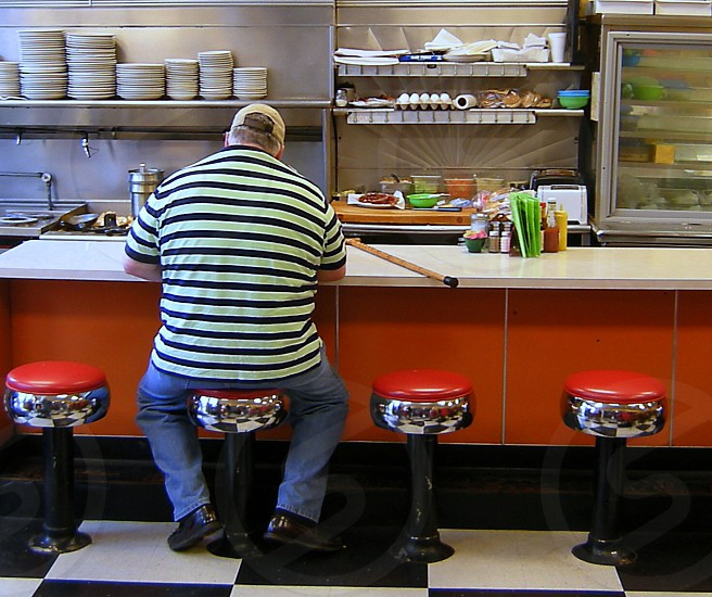Large man on barstool in diner photo