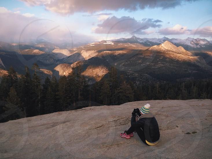 woman sitting on top of grey rocks photo