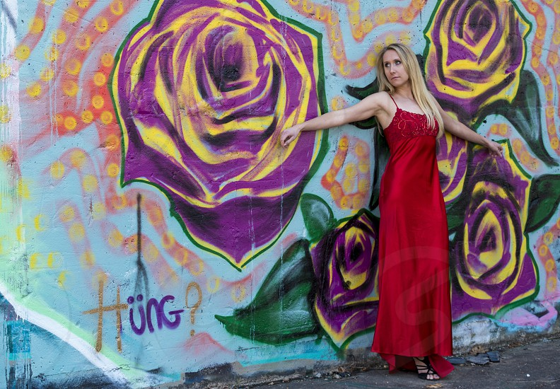 Beautiful young woman in red formal dress posed in a warehouse factory with gritty and colorful graffiti.  photo