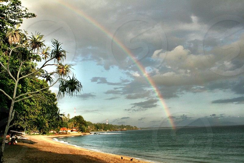 Rainbow over the water beach sun beautiful landscape sands sky cloud  photo
