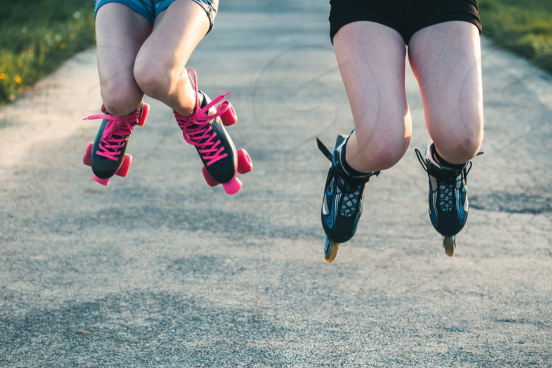 Teenage girls having fun rollerskating jumping spending time together on summer day photo