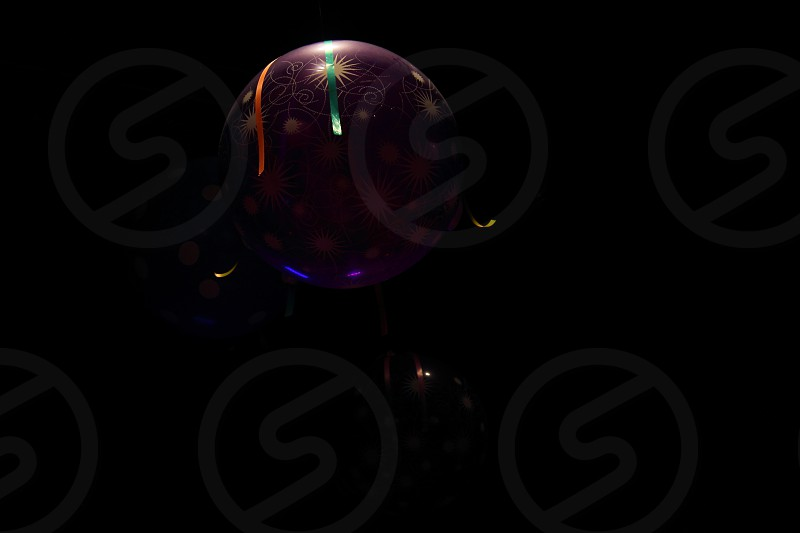 balls hanging from the ceiling in low light  photo
