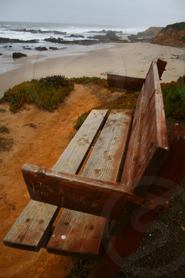 bench pn cliff overlooking beach  photo