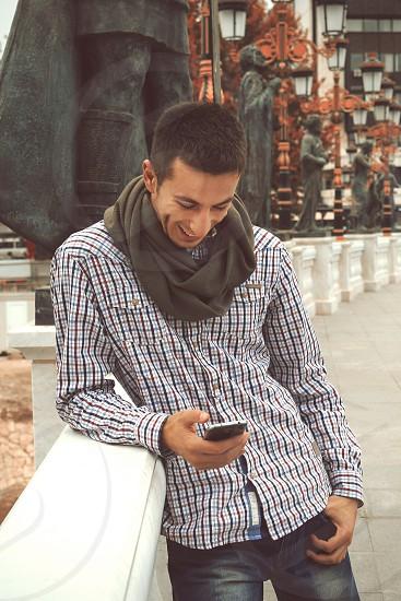 man fiddling phone smiling photo
