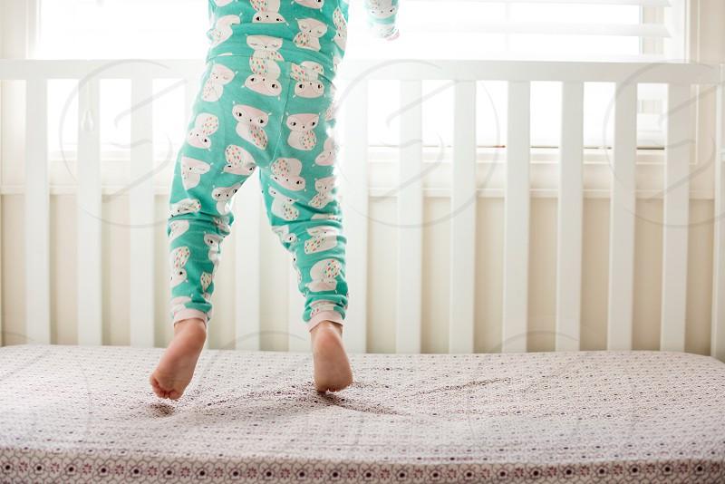 Toddler girl jump bed fun cute happy pajamas legs feet white crib photo