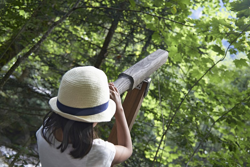 Young girl wearing a straw hat looking for birds through a binocular in a forest photo