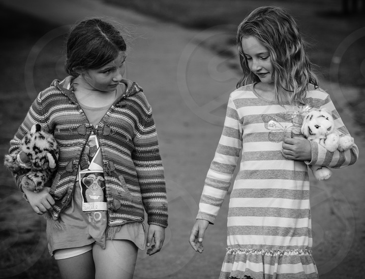Two young girls strolling and chatting. Friendship. Cuddly Toys. Childhood photo