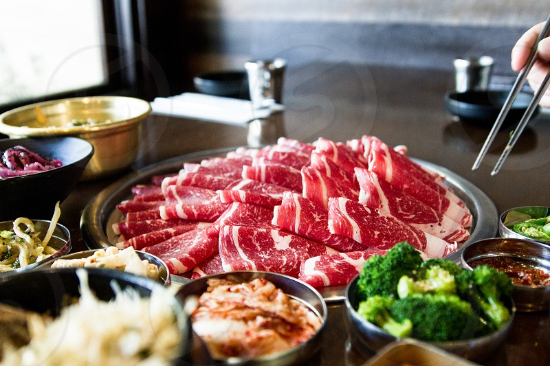 sliced meat beside broccoli in bowl on table photo