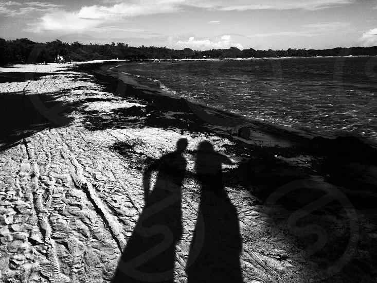 A pair of shadows in the sand.  photo