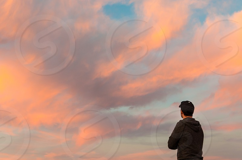 man wearing black hooded jacket standing under white clouds and blue sky photo