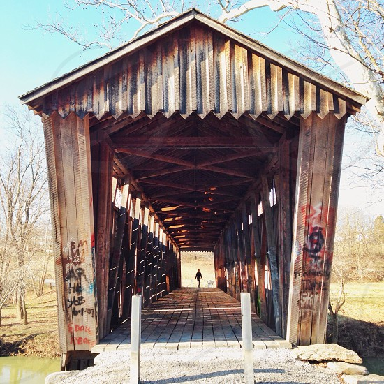person walking in brown wooden roofed bridge photo
