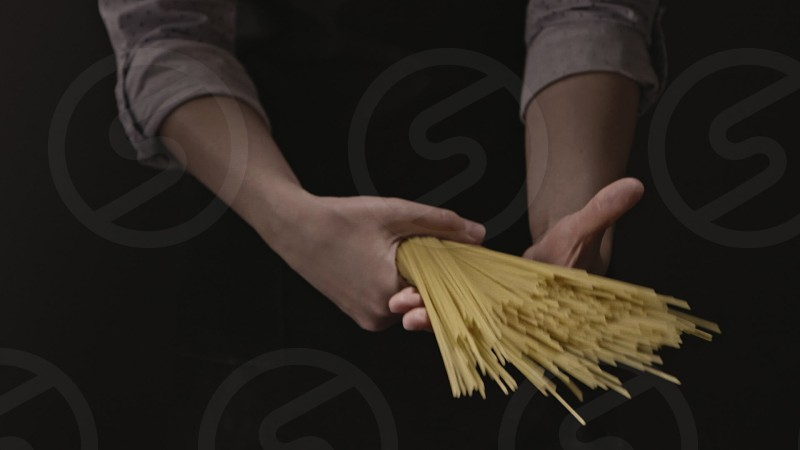 Chef female's hands hold the bunch of raw italian pasta on a black background. Slow motion Full HD video 240fps 1080p. Concept of italian food and cooking dinner. photo