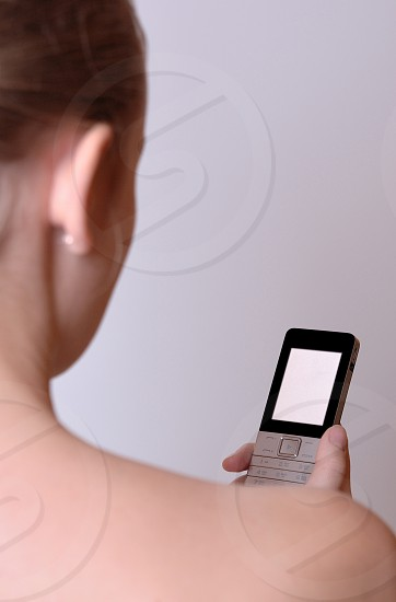 A young girl shooted from back is holding a cell phone with clear display. photo