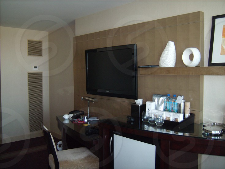 black flatscreen tv over black desk and wet bar in hotel room photo