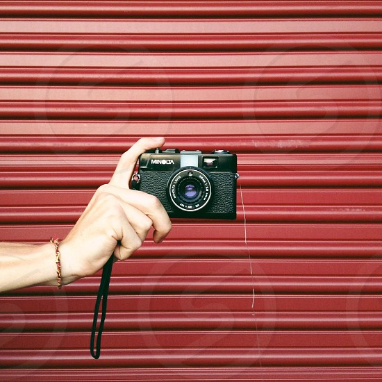 hand holding small black camera up in front of red wall photo