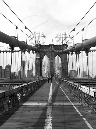 black white photograph of two figures walking on metal bridge photo