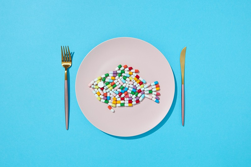 Many different pills and supplements as food on round white plate with fork and knife. Diet pills and supplements for dieting concept. Top view. photo