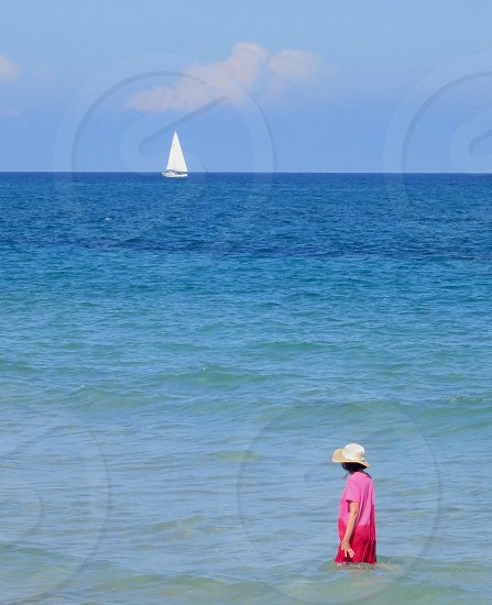 Woman in pink walking in ocean looking at sailboat on horizon photo