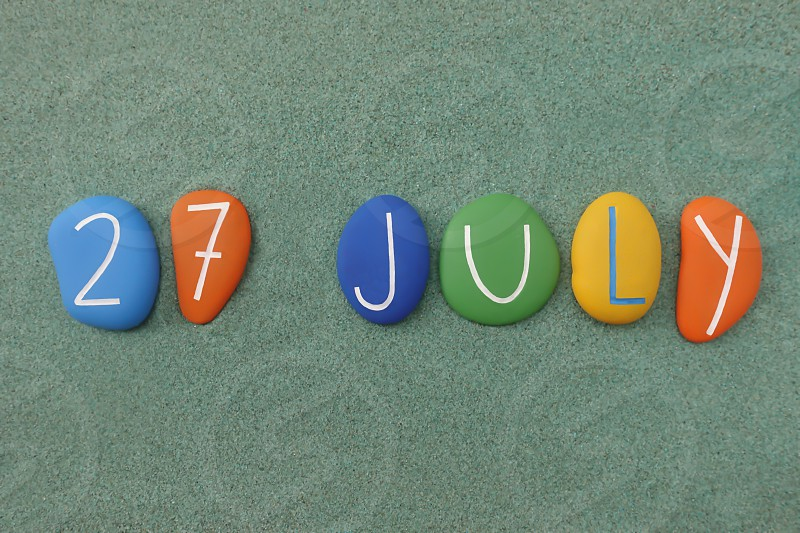 27 July calendar date composed with multi colored stones over green sand                            photo