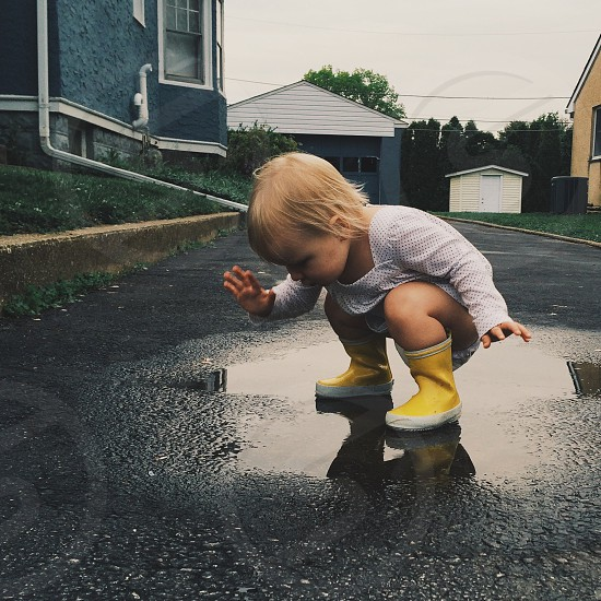 Cute little girl boots puddle playing reflection driveway photo