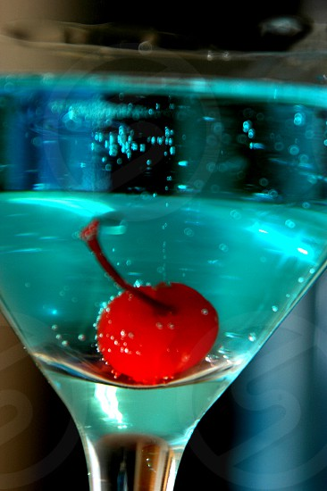 Red cherry in a blue martini photo