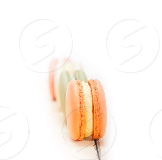colorful french macaroons over a white rustic wood table  photo