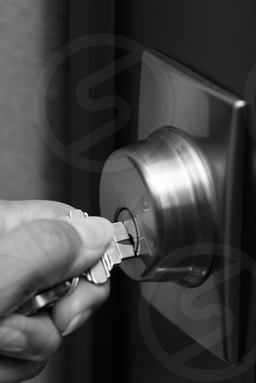 Key in hand locking door keys close up black and white opening lock lock and key safety home safety unlocking door house keys closing up vertical photo
